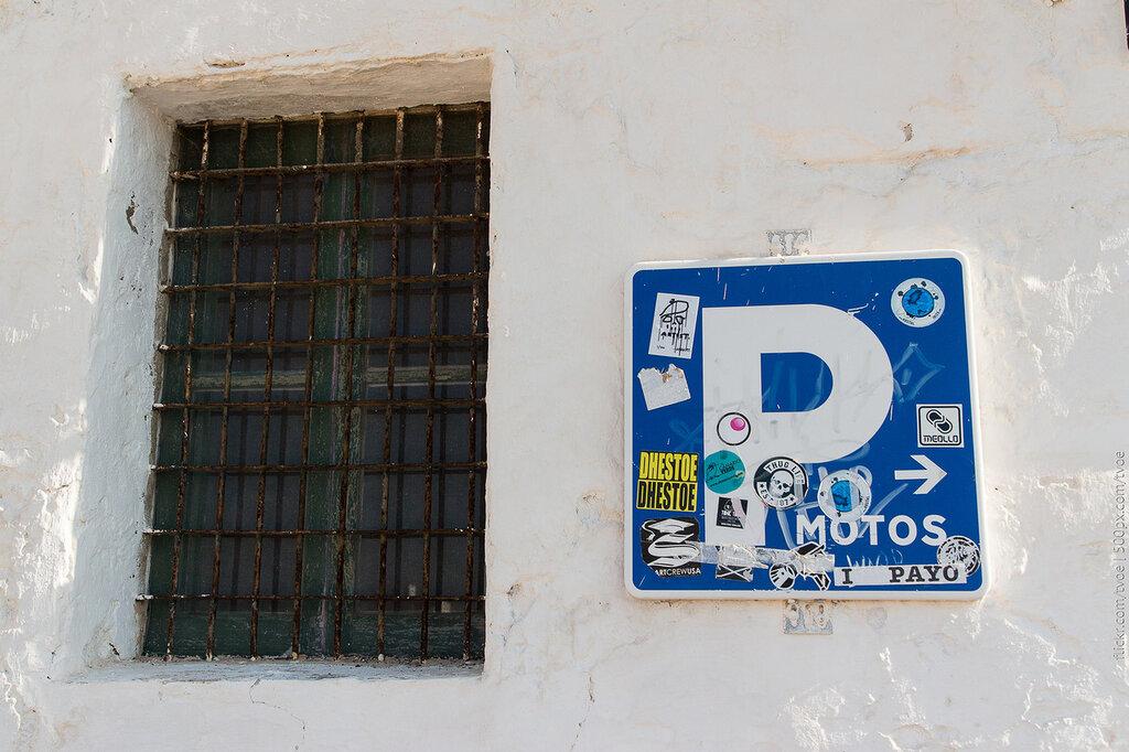 Знак парковки на ибице и древняя решётка на окне