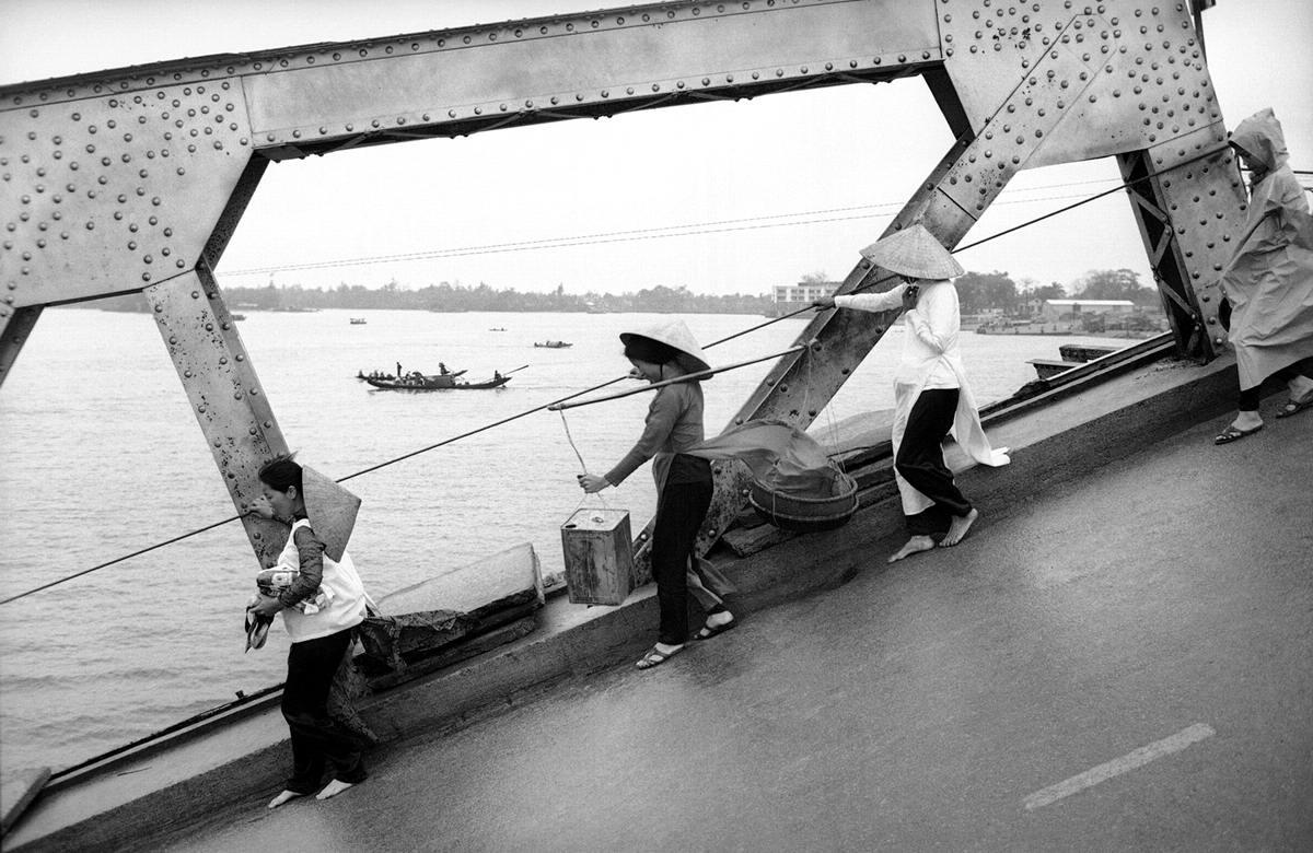Мирные вьетнамцы пересекают разрушенный мост в городе Hue