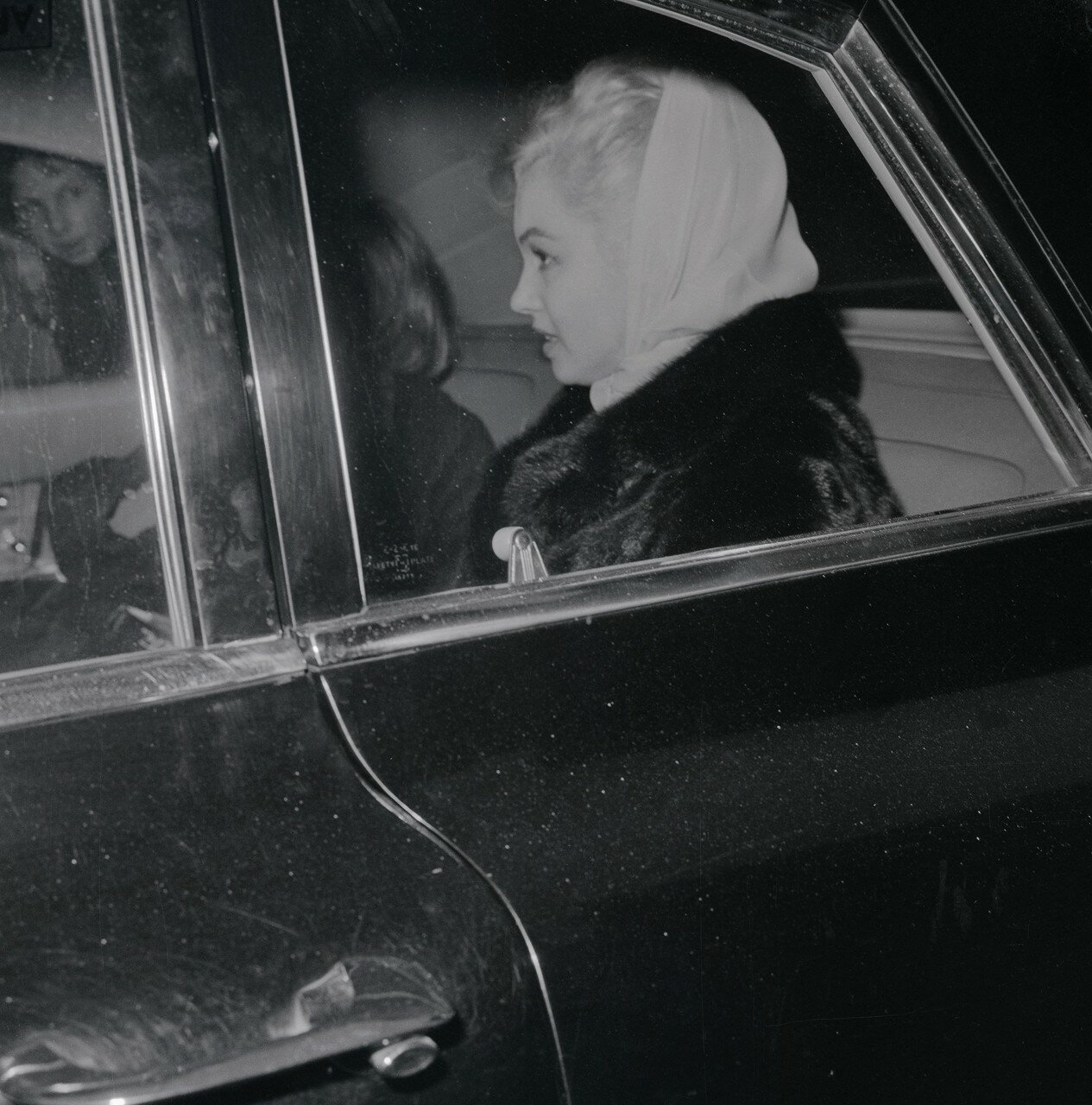 Marilyn Monroe Wearing a Scarf and Sitting in Car