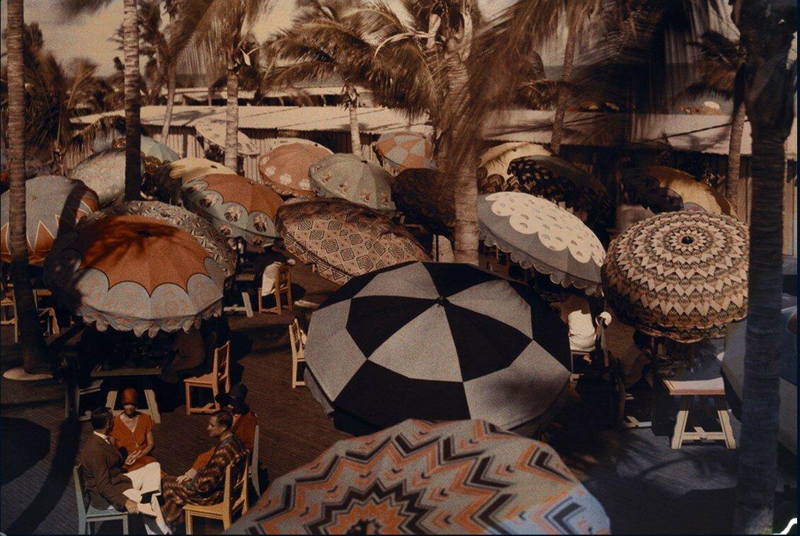 1930. США. Члены клуба на побережье океана под декоративными зонтиками