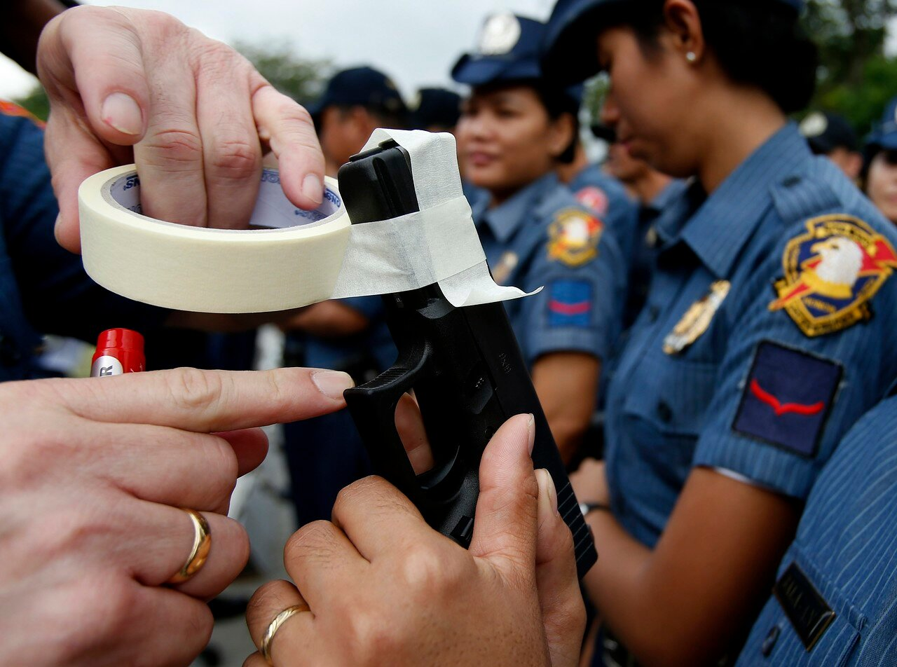 A police officer covers the muzzle of a service pistol of a policewoman with tape during a sealing of firearms ceremony at the National Capital Region Police Office in Taguig