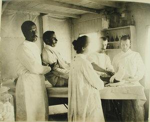 Медицинский персонал за перевязкой раненого в перевязочной Елизветградской баржи-лазарета