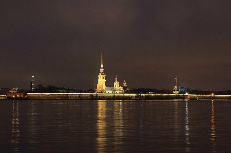 Шпиль Петропавловской крепости на Заячьем острове в Санкт-Петербурге, подсвеченный ночными огнями и его отражение в воде реки Невы.
