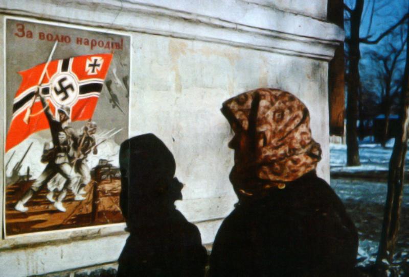 Жительница Харькова смотрит на пропагандистский немецкий плакат