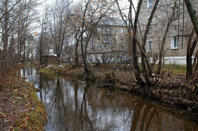 Жилые кирпичные пятиэтажки в нескольких метрах от спрямлённого русла реки Плоской в Коминтерне