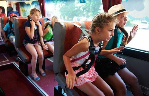 Дети испытывают работу ремней безопасности в специальном автобусе