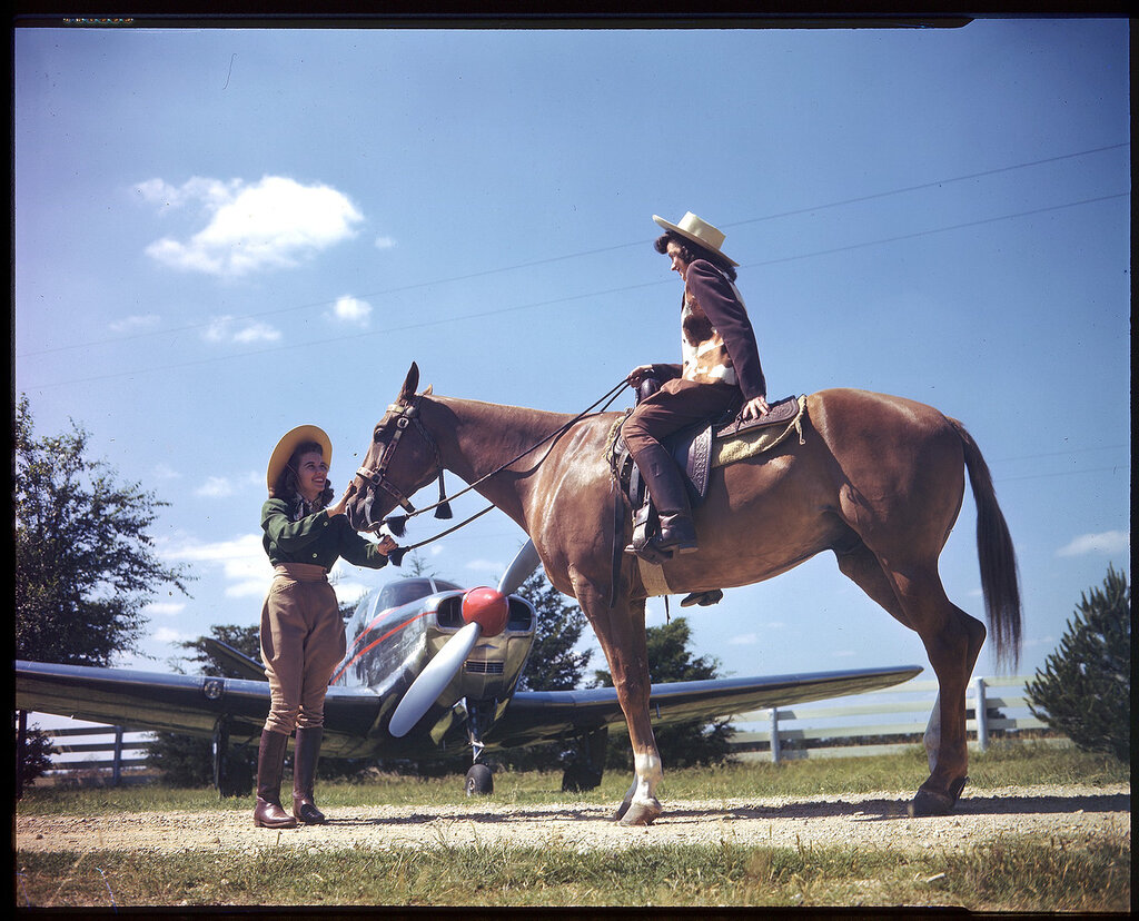 Beech Bonanza 35 (rn NX80040) parked at a horse ranch. A woman is posed sitting on a horse with another woman posed standing holding the rein