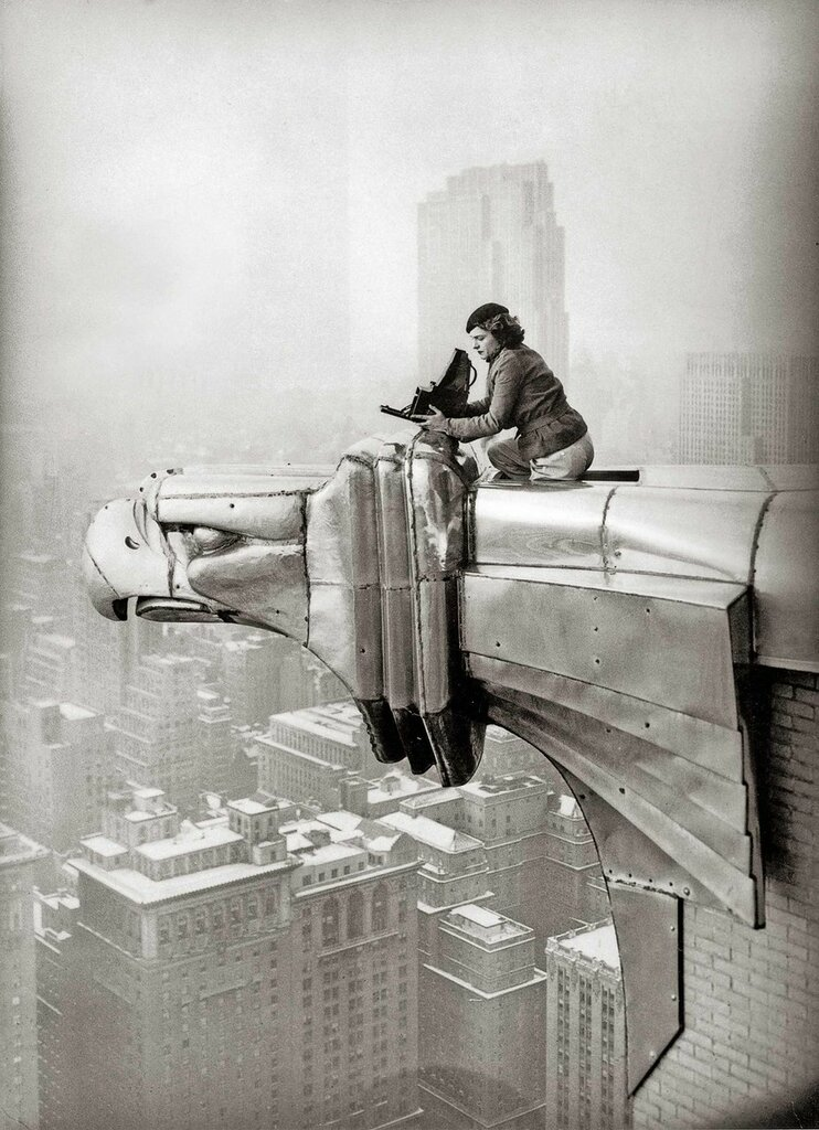 Margaret Bourke-White (1904–1971) perches on an eagle head gargoyle at the top of the Chrysler Building and focuses a camera, New York, 1935.jpg