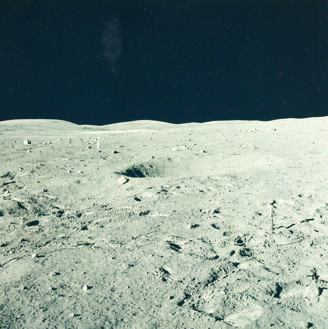 Янг с помощью троса с крючком опустил на лунную поверхность чемоданчик с фотокамерами и начал спускаться по лестнице. На снимке: место посадки