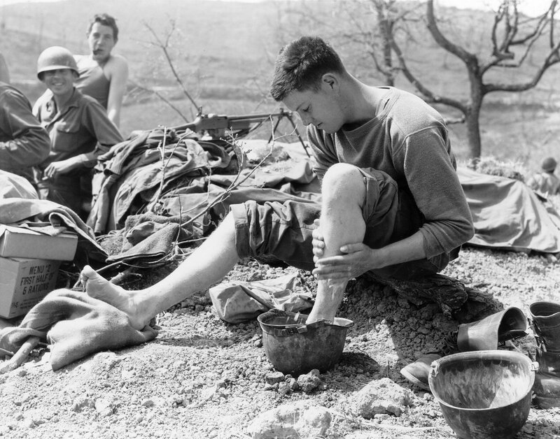 1945 April. Private First Class Lawrence Lucas, 604th Field Artillery, 10th Mountain Division, rests close to the front lines during the Italian Campaign in Bologna Province, Italy. He sits and washes his feet in his helmet.