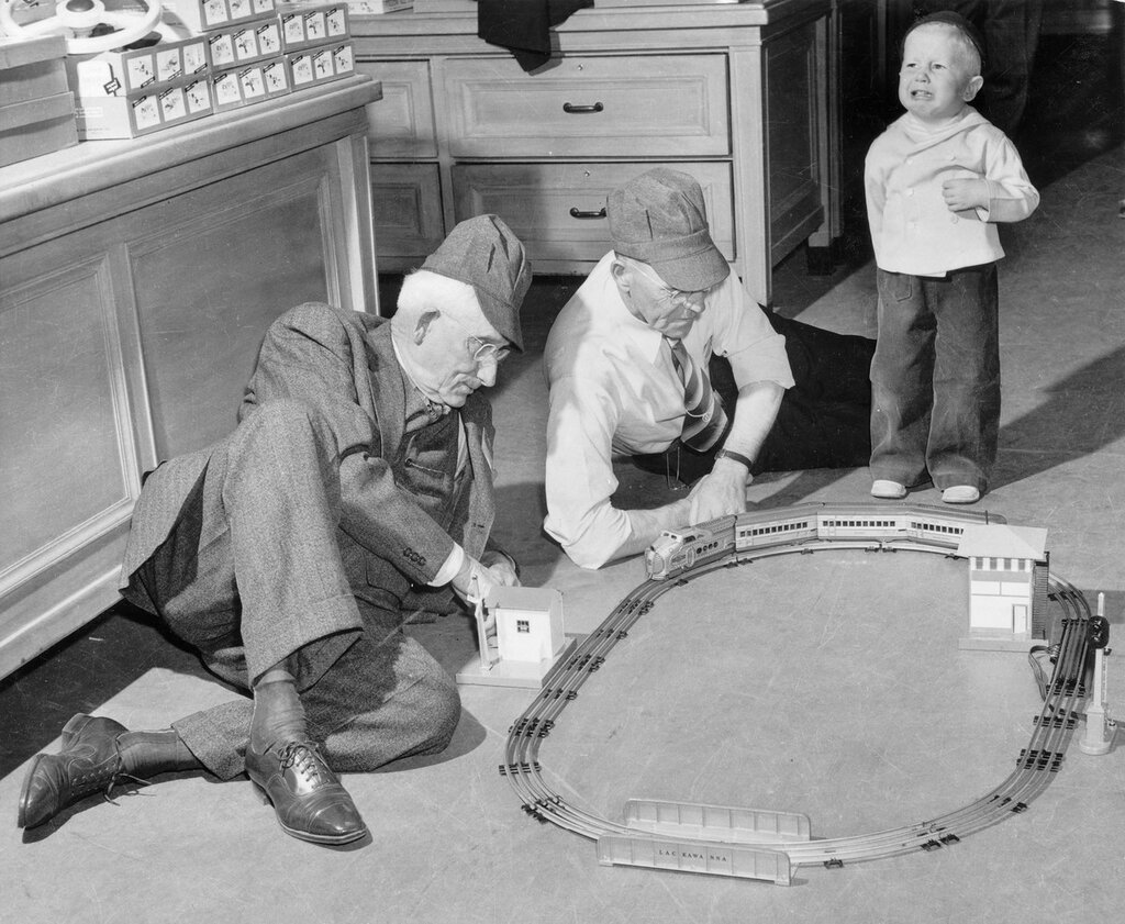 Two old men as they play with a 'Union Pacific' railroad set, between 1940 and 1950