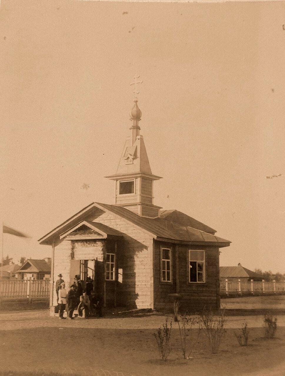 83. Группа посетителей выставки у модели церкви-школы