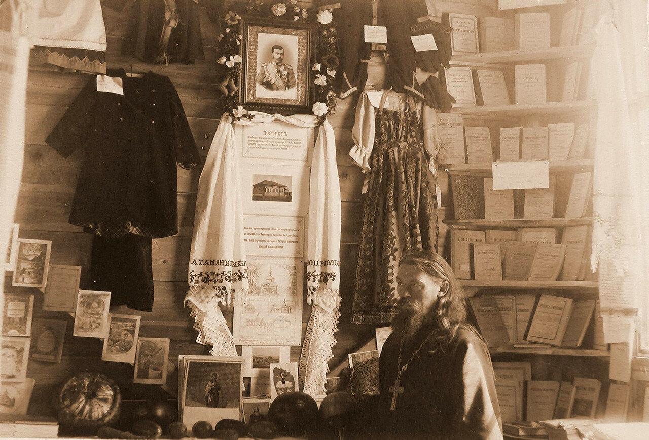 85. Священнослужитель у стенда со школьными принадлежностями и учебниками и экспонатами выставки
