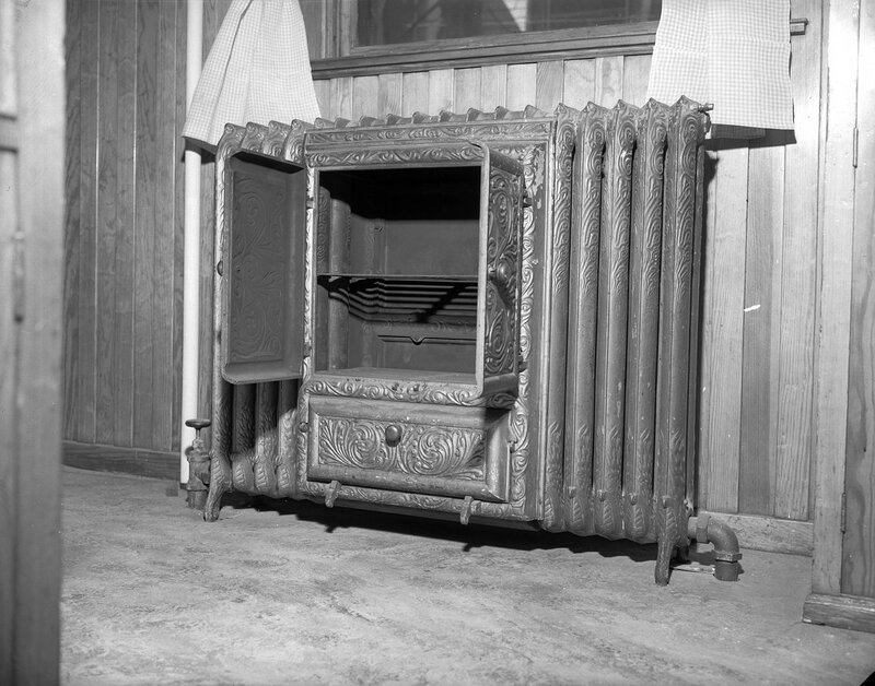 Stove and radiator at 909 Grant Street in the Capitol Hill neighborhood of Denver, Colorado. A metal shelf is in the oven portion of the radiator. between 1940 and 1950