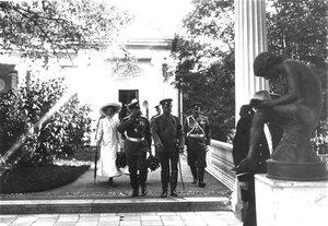 Император Николай II и сопровождающие его лица выходят из Агатовых комнат во время посещения Царскосельской Юбилейной выставки.