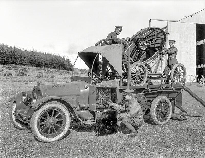 San Francisco circa 1922. 'Army car with carriage-mounted searchlight.' A military-grade Cadillac at the Presidio next to an aircraft hangar