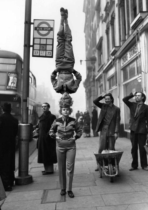 Two members of the Bertram Mills Circus walk head-to-head at Hammersmith Broadway in London, 1953.jpg