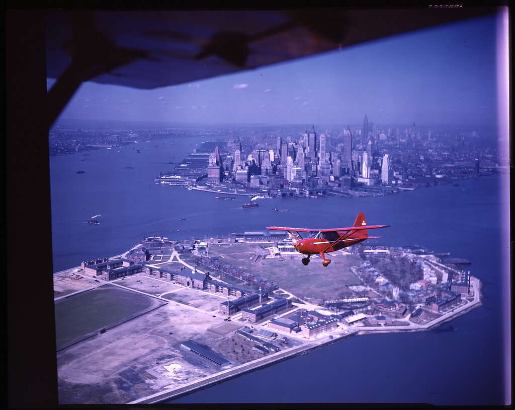 Stinson 108 Voyager (rn NC 26213) in flight over Governors Island, New York, NY