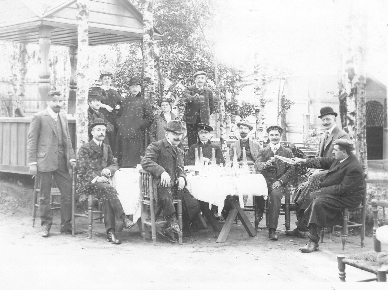 11. Группа участников автопробега в саду трактира за столиками