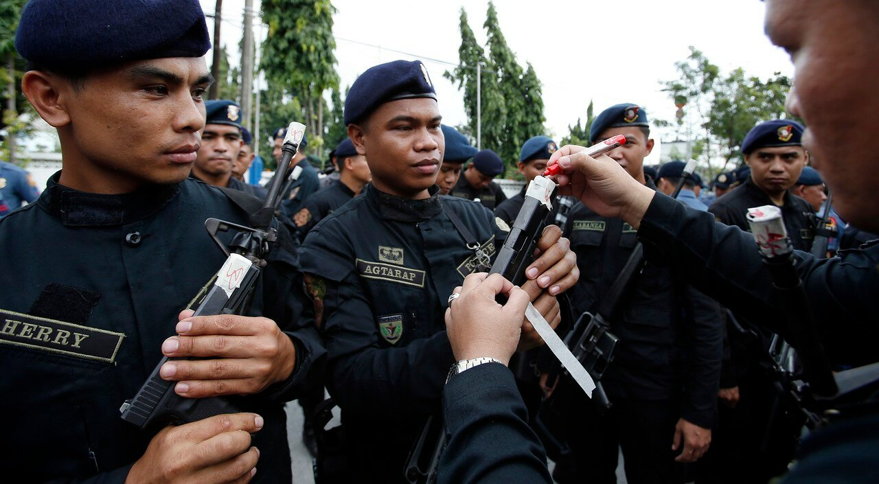 A Philippine National Police SWAT team leader signs a sealed muzzles of the firearms of his men at the National Capital Region Police Office in Taguig