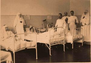 Старший врач лазарета и сопровождающий его медицинский персонал во время обхода в одной из палат.