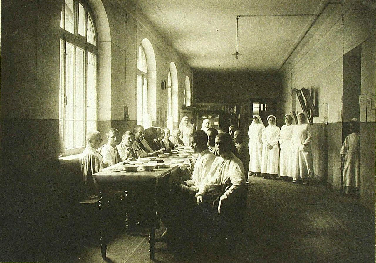 15. Раненые в столовой, оборудованной в одном из коридоров госпиталя; слева- сестры милосердия