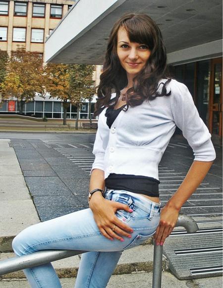 Девчонка шатенка возле школы в джинсах