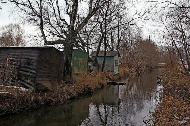 Старые гаражи и деревья без листьев над спрямлённым руслом реки Плоской в Коминтерне