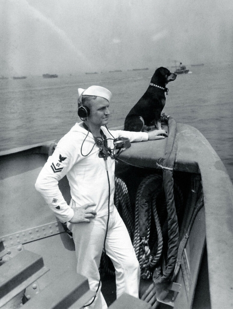 Sinbad, sentry dog for the US Coast Guard cutter, USCGC Campbell (WPG-32), and a crewman keep their eyes on the rest of the convoy, probably circa 1943.