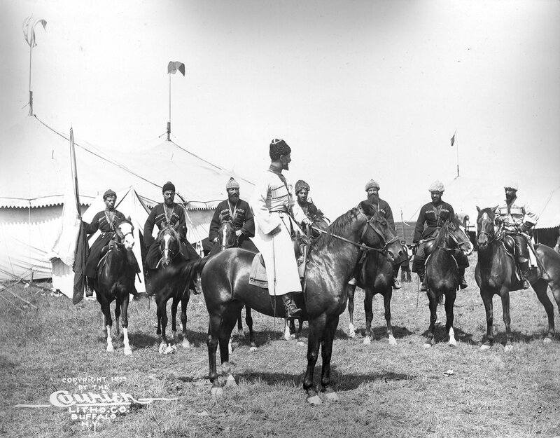 A group of Russian Georgian Cossacks pose on horseback in a camp for Buffalo Bill's Wild West Show. David Kadjaia, sits on his horse in front of the group.1899