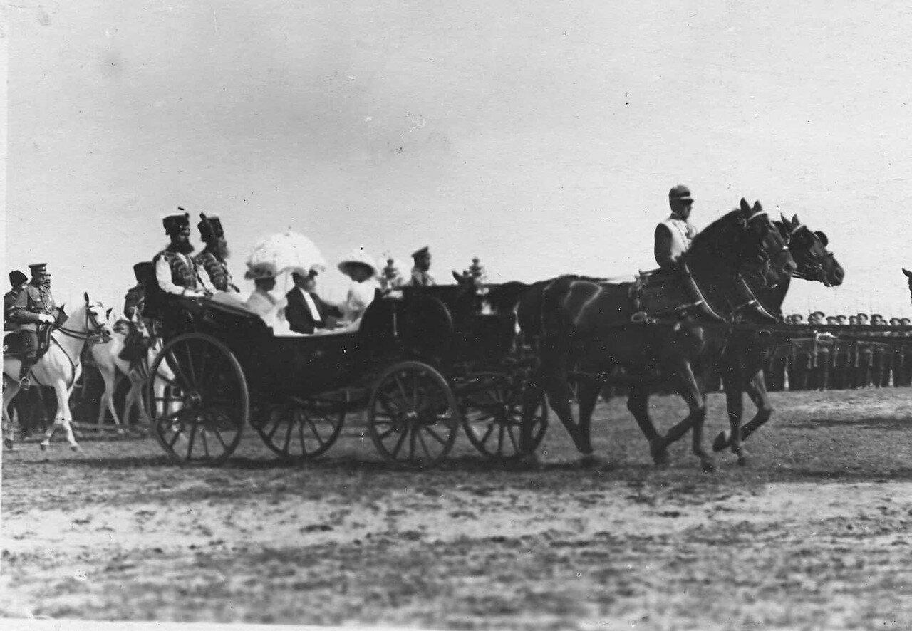 82. Император Николай II (верхом, за коляской), Р. Пуанкаре с членами императорской фамилии (в коляске) направляются к месту парада войск. Красное Село
