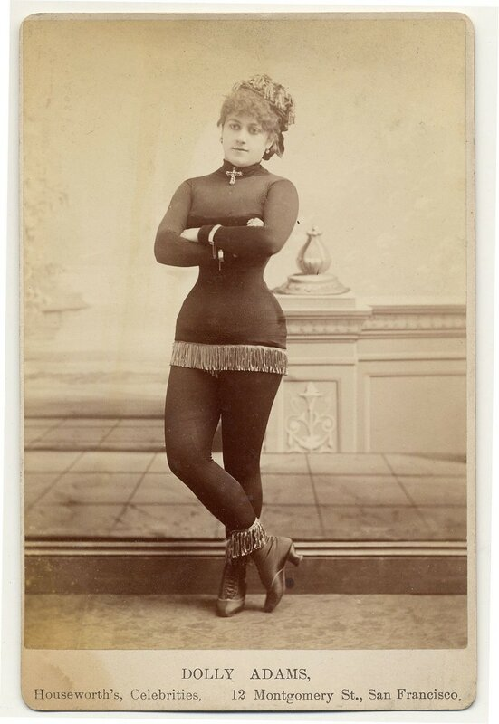 1890. Dolly Adams fringe at bottom of short costume, tights, short heeled boots topped with fringe, cross at neck, cap