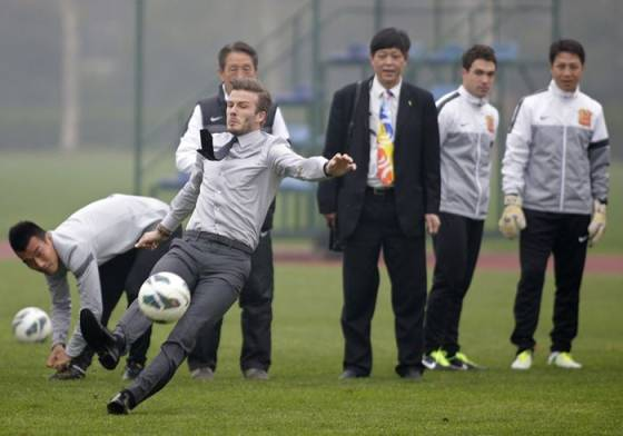 Дэвид Бекхэм упал в костюме и галстуке на футбольном поле