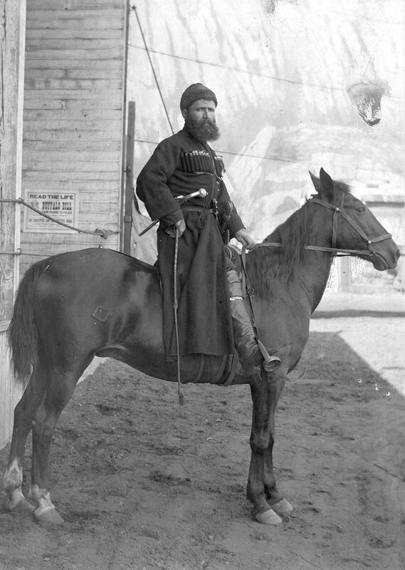 Russian Georgian Cossack, Ermile Antadze, poses on horseback in the foreground in front of a backdrop with a landscape scene painted on it for Buffalo Bill's Wild West Show, 1901
