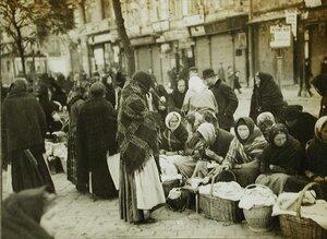 Местные жители делают покупки у уличных торговок.