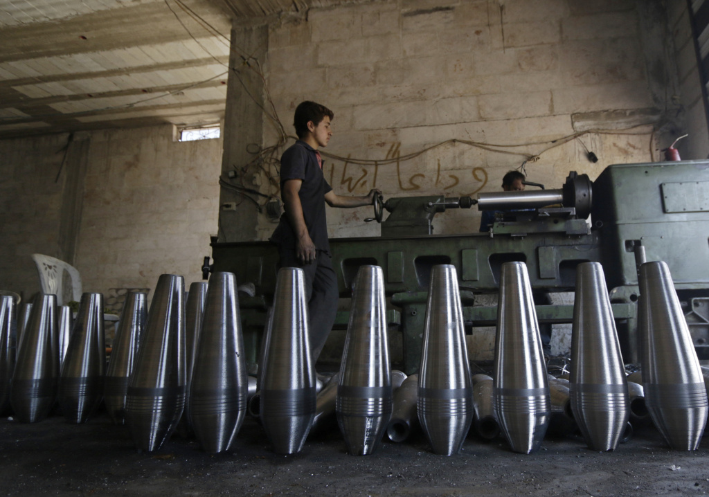 Rebel fighters make improvised mortar shells inside a weapons factory in Idlib