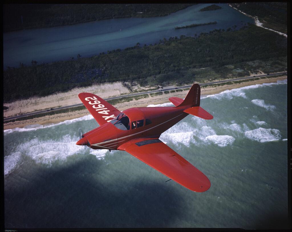 Johnson (TX) Rocket 185 (rn NX41662) in flight over coastline, probably somewhere over Long Island, New York