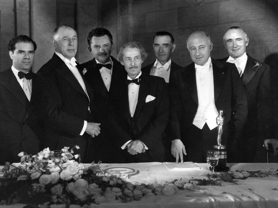 1936. Дэвид Уорк Гриффит (награда за выдающиеся заслуги), ведущий цуремонии Фрэнк Капра, актеры Джин Хершолт и Генри Вольтхолл