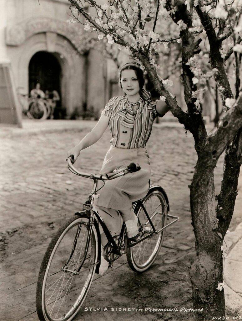 Sylvia Sidney rides a bike, holds a tree.jpg