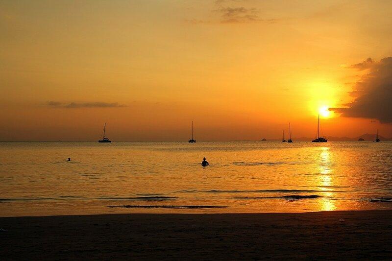 Закат на пляже Ао Нанг: садящийся шар солнца и яхты на горизонте