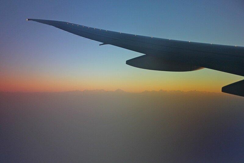 Рассвет над Гималаями: солнце поднимается над горной цепью, в кадре крыло самолёта и облака