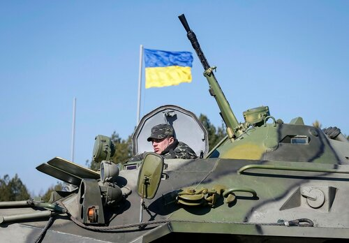 A Ukrainian soldier rides on an armoured personnel carrier during a military exercise near the village of Goncharivske