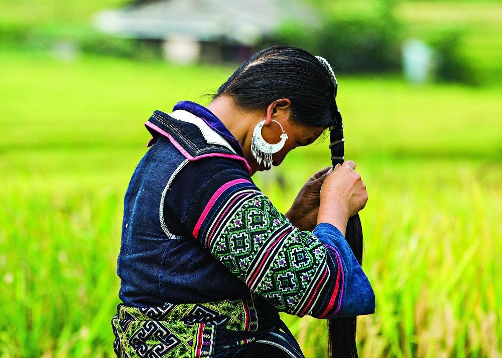 Женщина племени хмонг укладывает волосы в деревне Сапа.