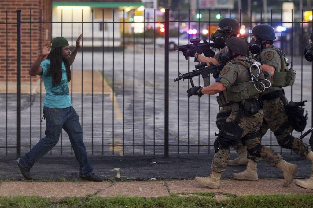 A man backs away as law enforcement officials close in on him and eventually detain him during protests over the death of Michael Brown, an unarmed black teenager killed by a police officer, in Ferguson, Mo.