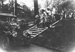 Император Николай II и сопровождающие его лица спускаются к машине после осмотра Царскосельской Юбилейной выставки.