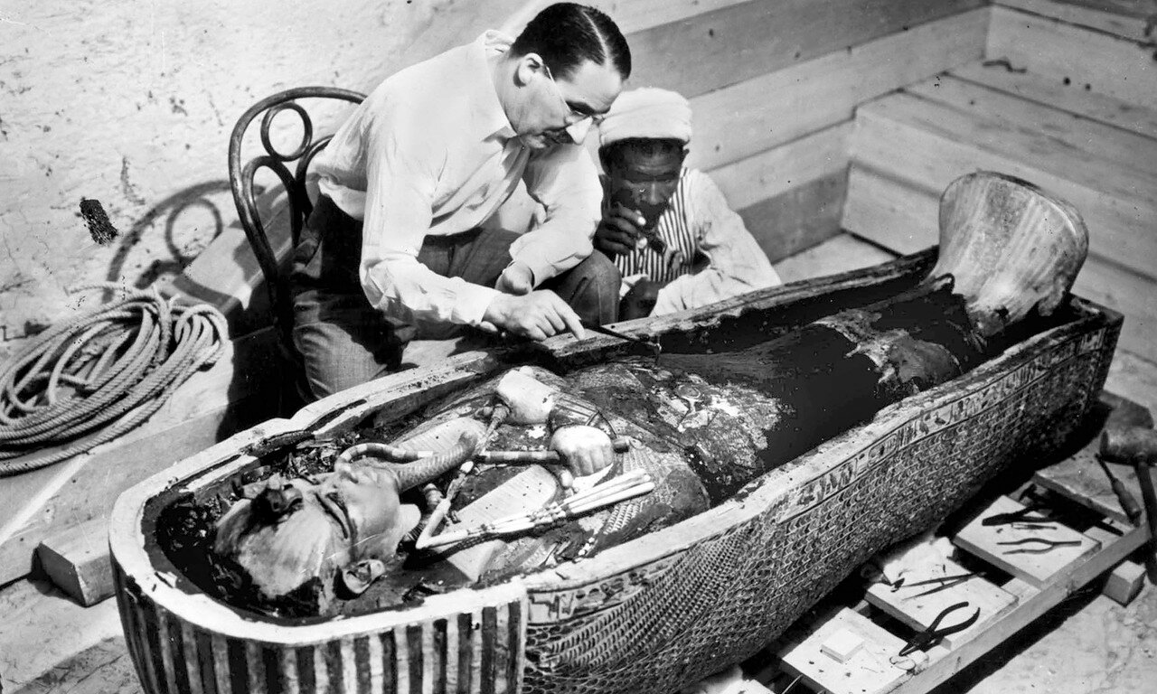 Британский археолог Говард Картер и египетский помощник исследует саркофаг с телом фараона Тутанхамона в Долине царей близ Луксора