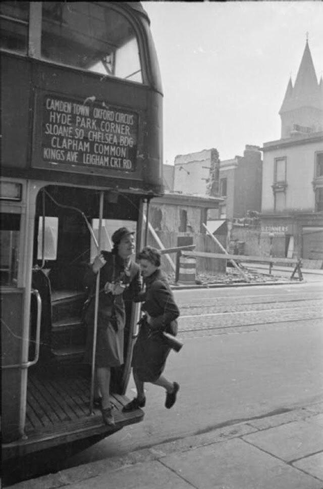20. Кондуктор помогает Оливии запрыгнуть в автобус по пути на работу. Фотография, скорей всего, сделана на Фулхэм Роуд