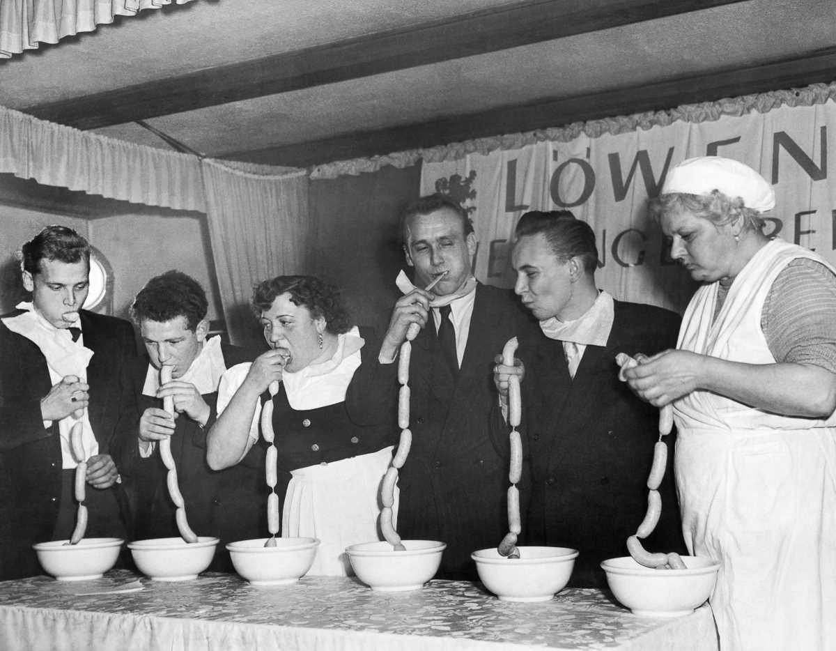 11. 19 ноября 1952 года. Конкурс по поеданию сосисок в Мюнхене, Германия. Победитель (второй слева)