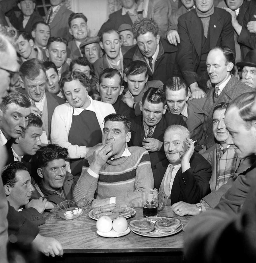 14. 1958 год. Зрители смотрят, как Джо Стил принимает участие в конкурсе по поеданию пищи.