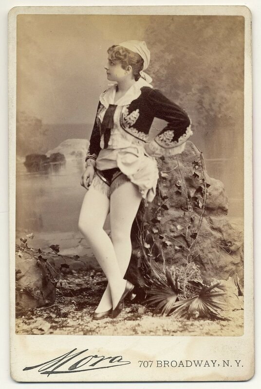 1890. Pauline Hall in short, Greek style costume, flat shoes.